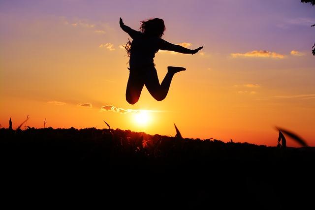 Postać skacze na tle zachodu słońca