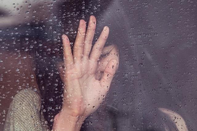 Kobieta patrząca przez okno na deszcz